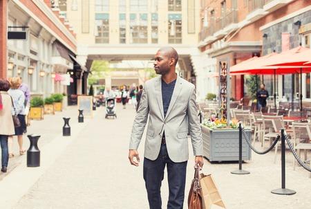 Photo pour Happy man with shopping bags walking on a street - image libre de droit