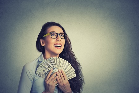Closeup portrait happy excited successful young business woman holding money dollar bills in hand isolated grey wall background. Positive emotion facial expression feeling. Financial reward