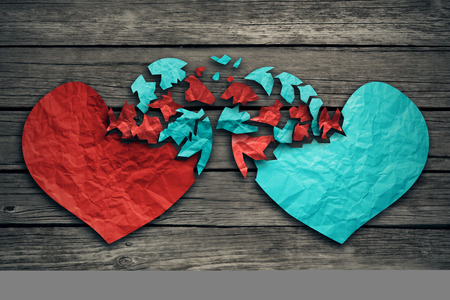 Foto de Romantic relationship concept as two hearts made of torn crumpled paper on weathered wood as symbol for romance attachment and exchange of feelings and emotions of love. - Imagen libre de derechos