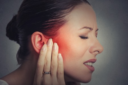 Foto für Tinnitus. Closeup up side profile sick female having ear pain touching her painful head isolated on gray wall background - Lizenzfreies Bild
