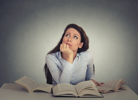 Closeup portrait annoyed, bored, tired, woman, funny student sitting at desk with many books looking up fed up of studying isolated on gray wall background. Face expression, emotion, reaction