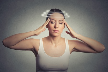 Closeup portrait young woman with vertigo. Young female patient suffering from dizziness isolated on gray wall background