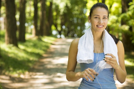Portrait young happy attractive smiling fit woman with white towel resting after sport exercises outdoors on a background of park trees. Healthy lifestyle well being wellness concept