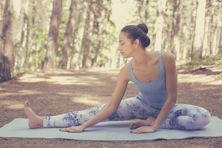 Foto de Stretching woman in outdoor exercise smiling happy doing yoga stretches after running. Beautiful happy smiling sport fitness model outside on summer spring day - Imagen libre de derechos