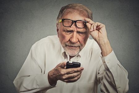 Closeup portrait headshot elderly man with glasses having trouble seeing cell phone has vision problems. Bad text message. Negative human emotion facial expression perception. Confusing technology