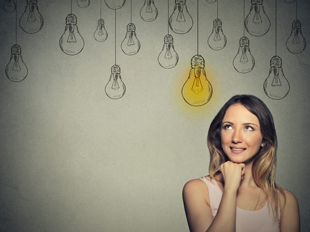 Photo for Happy smart girl with solution lightbulb above head - Royalty Free Image