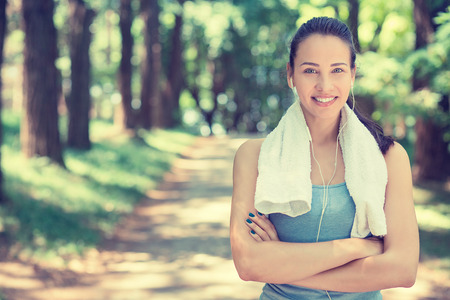 Portrait young attractive smiling fit woman with white towel resting after workout sport exercises outdoors on a background of park trees.
