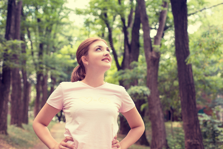 Photo pour Portrait young attractive smiling fit woman resting after workout sport exercises outdoor looking up enjoying fresh air standing on background park trees. Healthy lifestyle well being wellness concept - image libre de droit