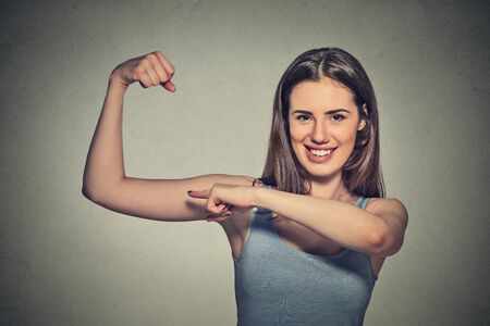 Closeup portrait beautiful fit young healthy model woman flexing muscles showing her strength isolated on grey wall background. Positive emotion facial expression feeling attitude perception wellbeing