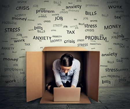 Portrait young woman hiding in the box working on computer laptop protected from daily life stressful situation
