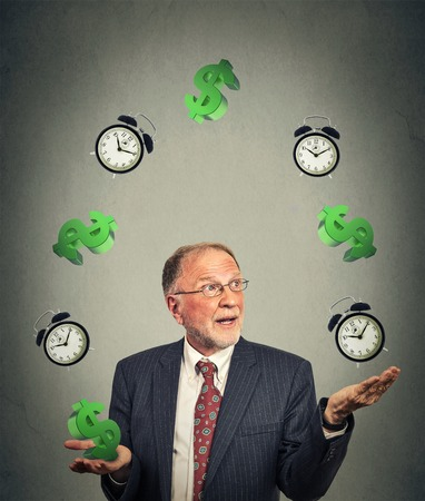 Senior business man in suit juggling multiple alarm clocks and dollar sings on gray office wall background. Time is money concept