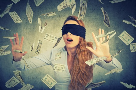 Blindfolded young entrepreneur businesswoman trying to catch dollar bills banknotes flying in the air on gray wall background. Financial corporate success or crisis challenge concept