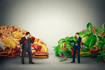 Vegetarian food representative fighting unhealthy junk fatty food guy with boxing gloves ready to punch each other. Diet battle nutrition concept idea