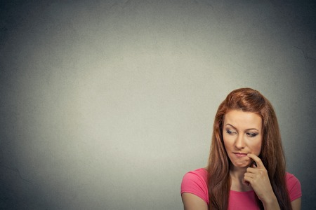 Headshot thoughtful skeptical jealous young woman isolated on gray background with copy space. Negative human emotion face expression