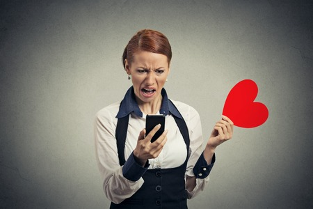 Portrait offended displeased young woman reading news on smart phone throwing away red heart isolated on gray wall background. Human facial expression emotion feeling reaction