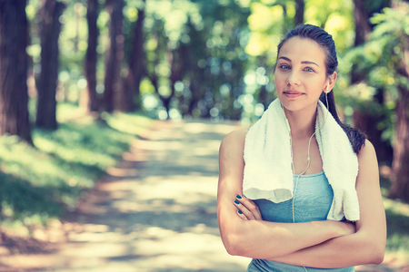 Portrait young attractive confident fit woman with white towel resting after workout sport exercises outdoors on a background of park trees. Healthy lifestyle well being wellness happiness concept
