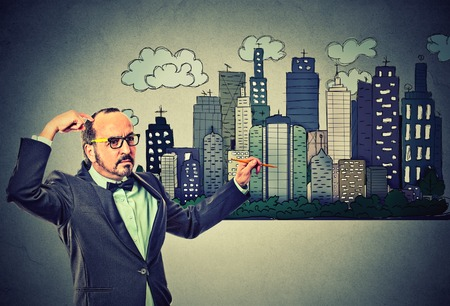 Man drawing city skyline on gray wall background. Real estate development, house market economy, investment opportunity concept