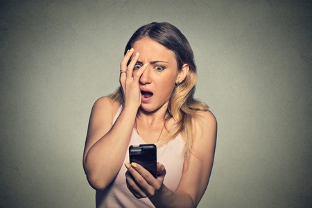 Photo pour Closeup portrait anxious scared young girl looking at phone seeing bad news photos message with disgusting emotion on her face isolated on gray wall background. Human reaction, expression - image libre de droit