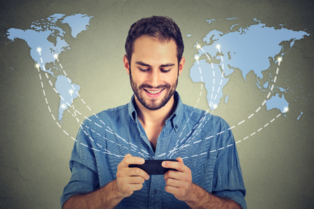 Modern communication technology mobile phone high tech, web connection concept. Happy business man holding smartphone connected browsing internet worldwide world map background. 4g data plan provider