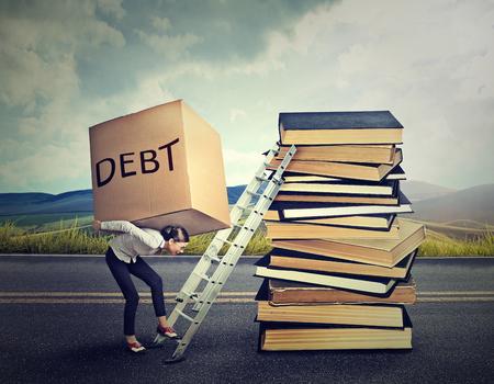 Foto de Student loan debt concept. Young woman with heavy box full of debt carrying it up the education ladder - Imagen libre de derechos