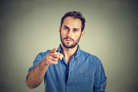 Portrait of a angry young man pointing finger at you camera gesture isolated on gray wall background