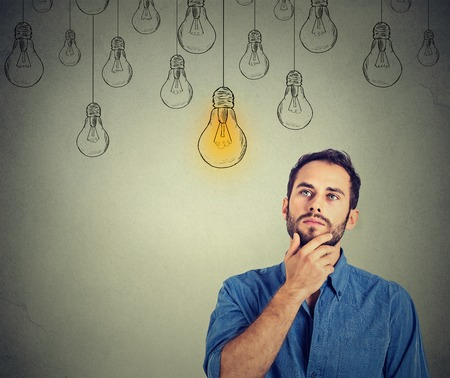 Foto de Portrait thinking handsome man looking up with idea light bulb above head isolated on gray wall background - Imagen libre de derechos