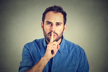 young handsome man giving Shhhh quiet, silence, secret gesture isolated on gray wall background