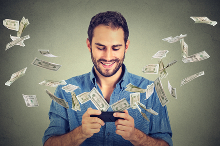 Technology online banking money transfer, e-commerce concept. Happy young man using smartphone with dollar bills flying away from screen isolated on gray wall office background.