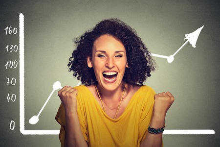 Young successful business woman pumping fists happy with wealth growth celebrates screaming isolated on gray wall background with growing graph. Financial freedom target success concept