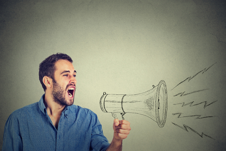 Photo pour Side portrait angry young man holding screaming in megaphone isolated grey background. Negative face expression emotion feeling. Propaganda, breaking news, power, social media communication concept - image libre de droit