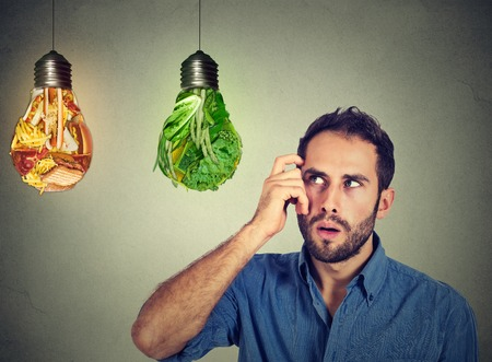 Puzzled man thinking looking up at junk food and green vegetables shaped as light bulbs making decision isolated on gray background. Diet choice right nutrition healthy lifestyle wellness concept