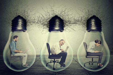 Photo pour Side profile company employees sitting in row inside electric lamp light bulb using laptop isolated on gray office wall background. Idea exchange network concept. Working conditions productivity - image libre de droit