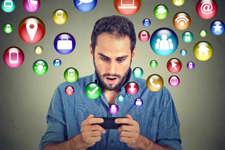 Photo for communication technology mobile phone high tech concept. Shocked handsome man using texting on smartphone application icons flying out of cellphone screen isolated on grey background. Face expression - Royalty Free Image