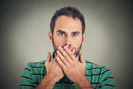 Photo pour Closeup portrait man with hand over his mouth, speechless, isolated on gray wall background - image libre de droit