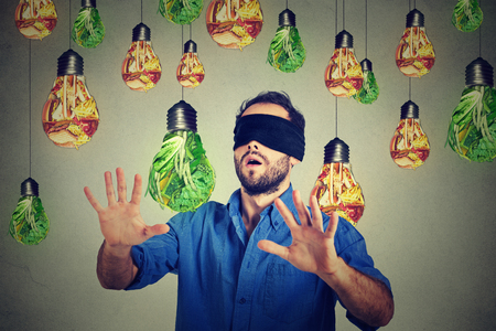 Photo for Blindfolded young man walking through light bulbs shaped as junk food and green vegetables isolated on gray wall background. Diet choice right nutrition healthy lifestyle concept - Royalty Free Image
