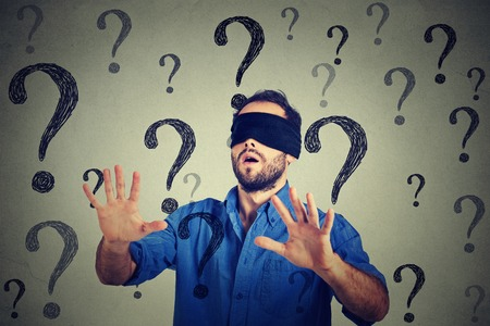 Photo pour Portrait business man blindfolded stretching his arms out walking through many questions isolated on gray wall background - image libre de droit