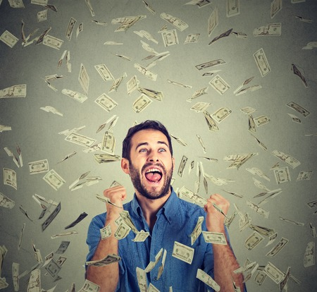 Photo pour Portrait happy man exults pumping fists ecstatic celebrates success screaming under money rain falling down dollar bills banknotes isolated gray background with copy space. Financial freedom concept - image libre de droit
