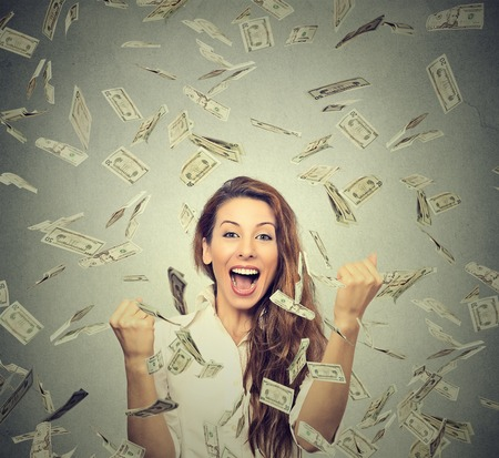Photo for Portrait happy woman exults pumping fists ecstatic celebrates success under a money rain falling down dollar bills banknotes isolated on gray wall background with copy space - Royalty Free Image