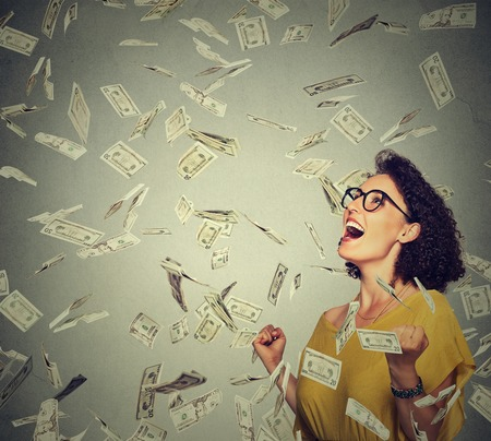 Photo for Portrait happy woman in glasses exults pumping fists ecstatic celebrates success under a money rain falling down dollar bills banknotes isolated on gray wall background with copy space - Royalty Free Image