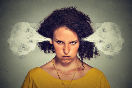 Closeup portrait of angry young woman, blowing steam coming out of ears, about to have nervous atomic breakdown, isolated gray background. Negative human emotions facial expression feelings attitude