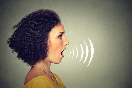 Side profile young woman talking with sound waves coming out of her mouth isolated on grey wall background. Human face expressions