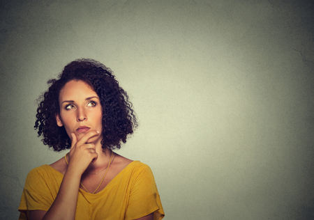 Woman thinking dreaming has many ideas looking up isolated on gray wall background.