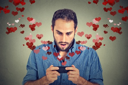 Foto de Portrait young handsome shocked man sending receiving love sms text message on mobile phone with red hearts flying away up isolated on grey wall background. Human emotions - Imagen libre de derechos