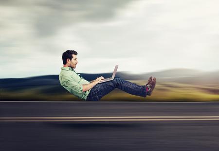 Foto de Fast internet concept. Autonomous self driving vehicle car technology. Levitating business man on road using laptop - Imagen libre de derechos