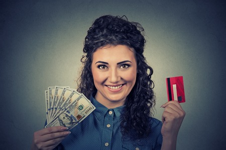 Photo pour Young woman shopping holding showing credit card and cash dollar banknotes bills - image libre de droit