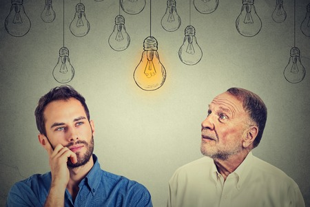 Cognitive skills concept, old man vs young person. Senior man and young guy looking at bright light bulb isolated on gray wall background