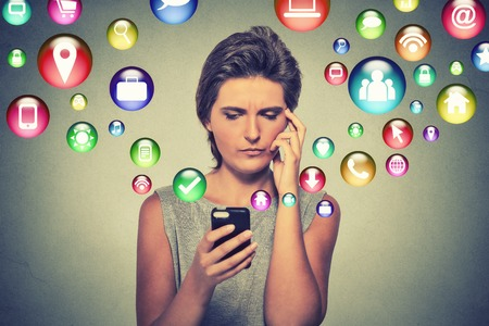 Photo for communication technology mobile phone high tech concept. Confused woman using texting on smartphone application icons flying out of cellphone screen isolated on gray background. Face expression - Royalty Free Image