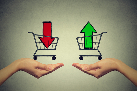 Photo pour Two hands with consumer baskets with up and down arrow signs isolated on gray wall background - image libre de droit