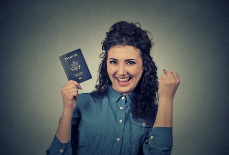 Portrait attractive young excited woman with USA passport isolated on gray wall background.