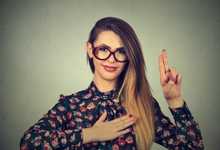 Photo pour Young woman in glasses making a promise isolated on gray wall background - image libre de droit